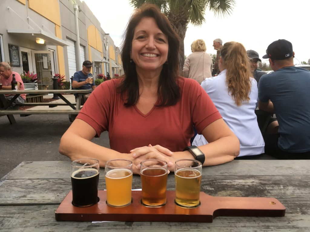 Best things to do in Fort Myers, Florida featured by top US travel blog, The Common Traveler: image of woman with flight of beer at Fort Myers Brewing Company - one of the best things to do in Fort Myers today