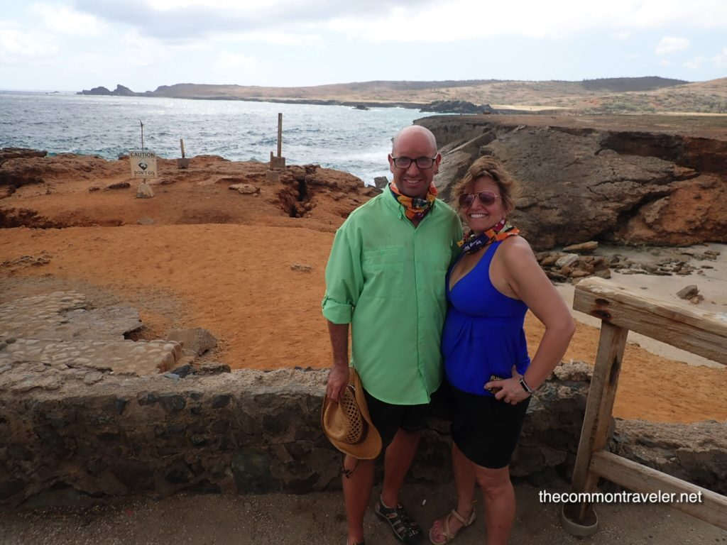 Aruba Sightseeing tips featured by top travel blog, The Common Traveler: Aruba Beaches and Desert couple in front of natural bridge, Aruba