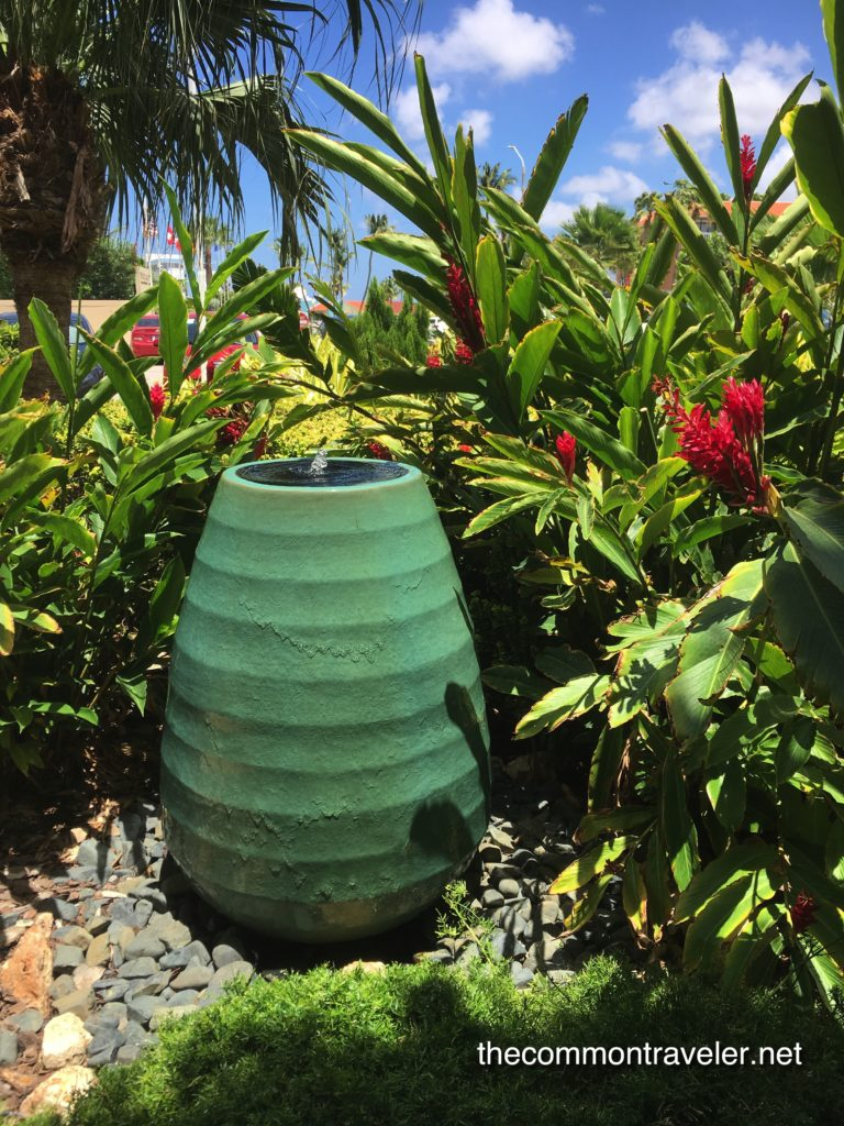 green vase water fountain surrounded by tropical plants