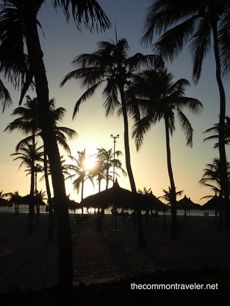sunset with palm trees and palapas