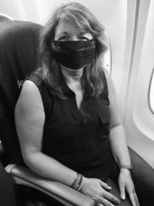 Sick While Traveling woman wearing mask on plane