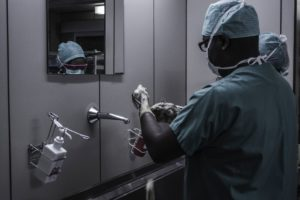 Sick While Traveling surgeon scrubbing hands with soap