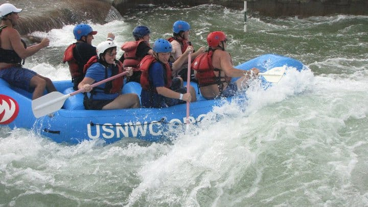 The Ultimate Weekend in Charlotte NC featured by top travel blog, The Common Traveler: Charlotte  people paddling on a blue whitewater raft
