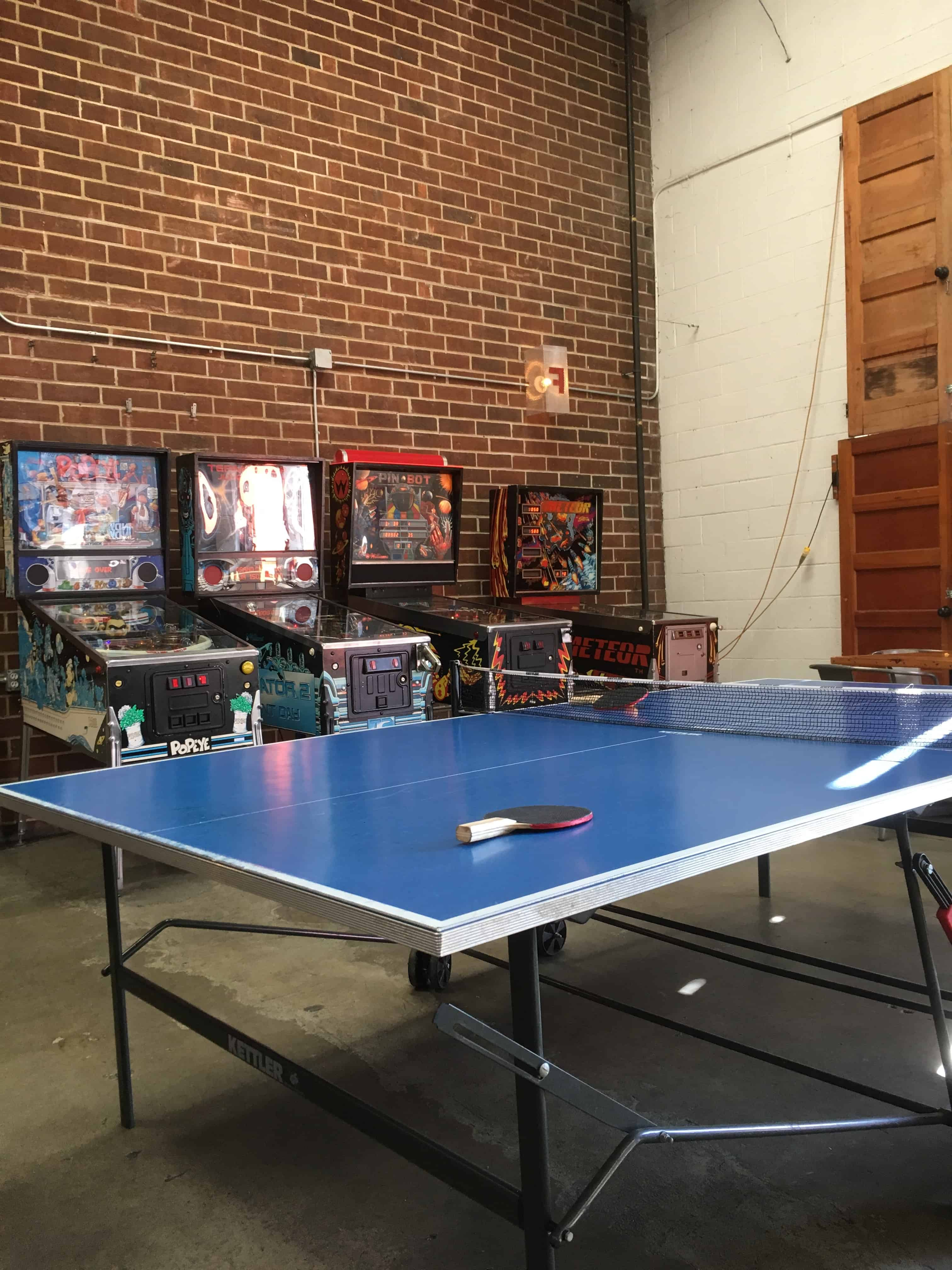ping pong table with arcade games in back