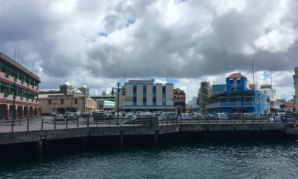 Unique Things to Do in Barbados on a Port Day featured by top US cruise blog, The Common Traveler: dock with colorful buildings in Barbados