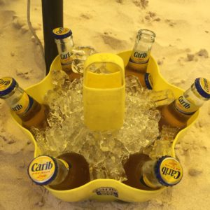 Unique Things to Do in Barbados on a Port Day featured by top US cruise blog, The Common Traveler: barbados bucket of Carib beer bottles in sand