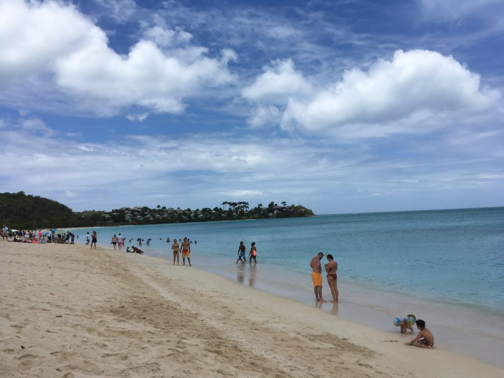 How to Enjoy Antigua  Beaches on a cruise port day, tips featured by top US travel blog, The Common Traveler: bathers at beach in Antigua
