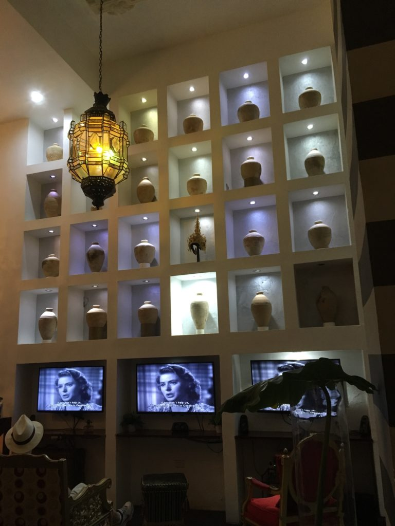 hotel in Old San Juan wall with jars and TVs showing the movie Casablanca