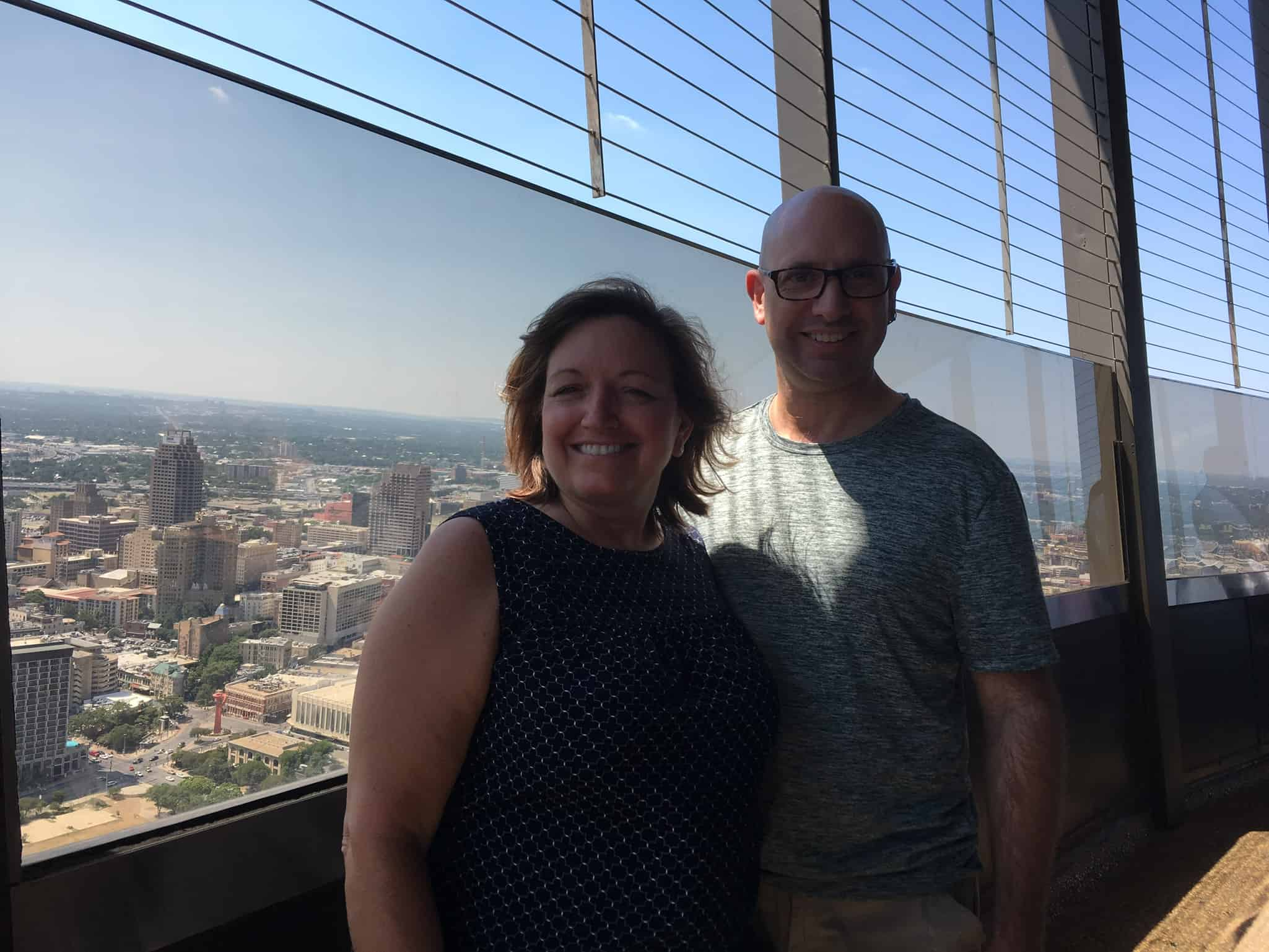 Visiting the Tower of the Americas in San Antonio TX, tips featured by top travel blog, The Common Traveler: Tower of the Americas woman and man on observation deck with San Antonio in background