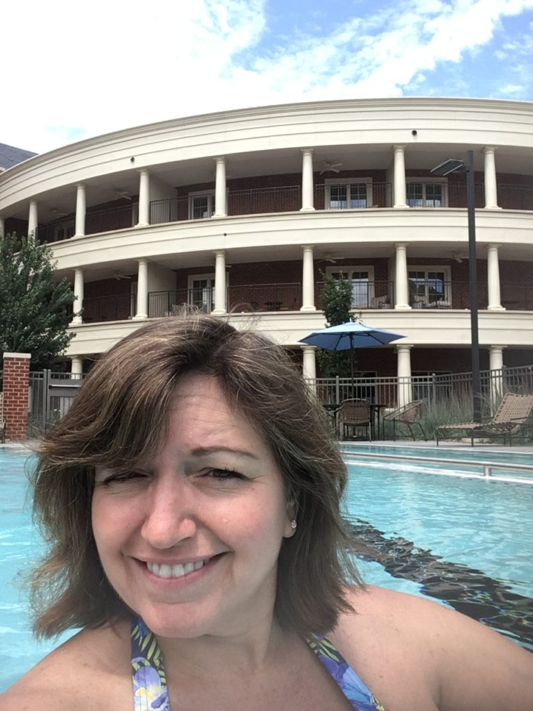 woman in pool with Rizzo Center in background