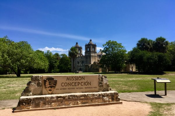 Tips for visiting San Antonio Missions shared by top US travel blog, The Common Traveler: San Antonio's Missions stone sign with words Mission Concepcion and old church in back