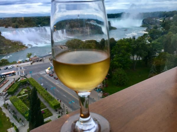 glass of wine in foreground with Niagara Falls in background