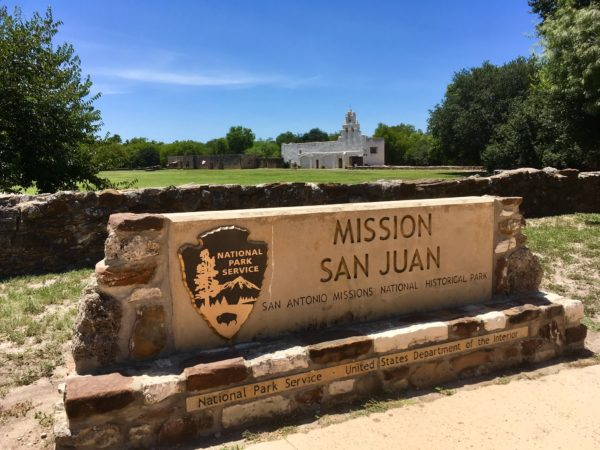 Tips for visiting San Antonio Missions shared by top US travel blog, The Common Traveler: San Antonio's Missions stone sign with text Mission San Juan and old church in back