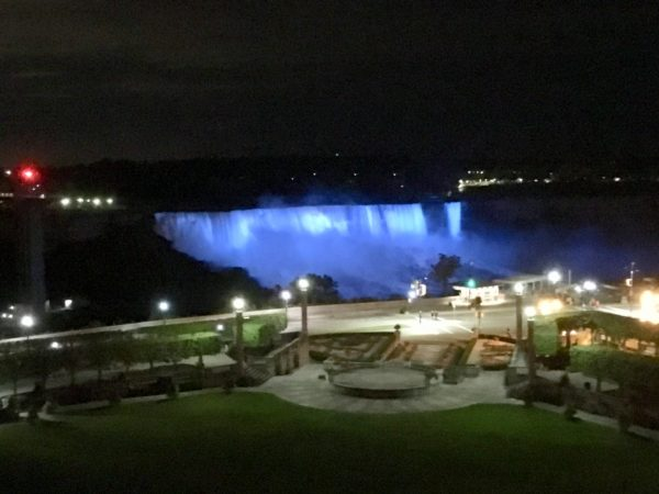 Day Trip to Niagara Falls - US and Canadian Sides featured by top travel blog, The Common Traveler: itinerary American falls lit up at night time.