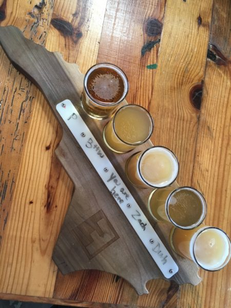 flight of beer on tray in shape of NC state