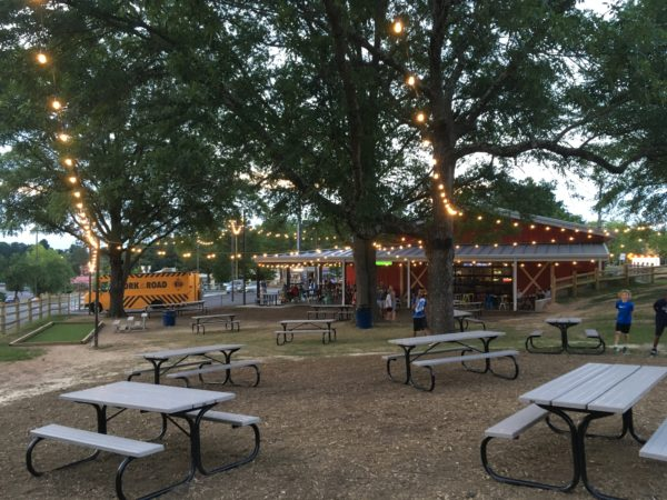 picnic tables in foreground with red barn, trees with lights and food trucks in background