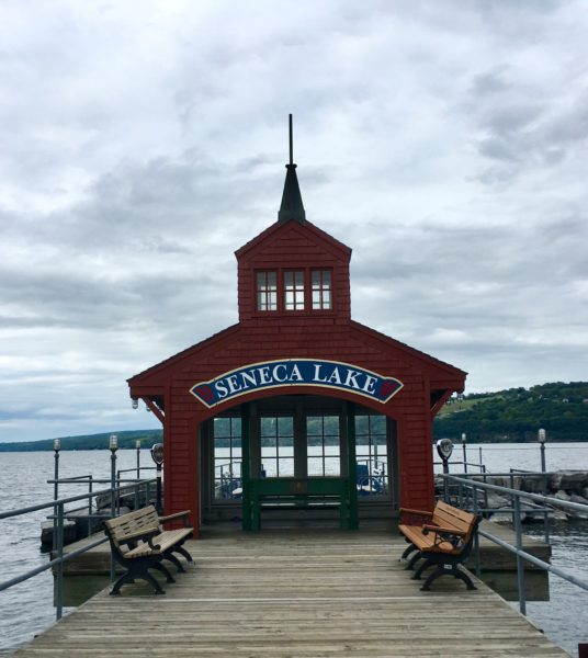 "red boat house on dock with ""Seneca Lake"""