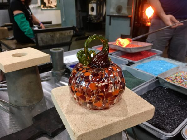 glass pumpkin with glass works in the background