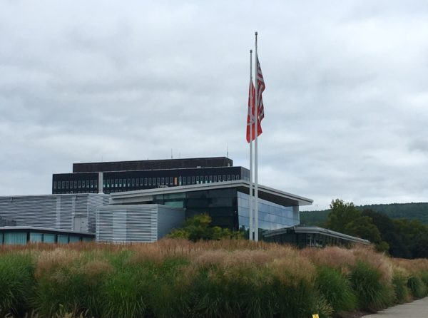 glass and metal building with flags out front - Corning Museum of Glass