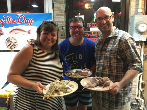 One Week in Belize featured by top US travel blog, The Common Traveler: woman and two men holding plates of fresh seafood