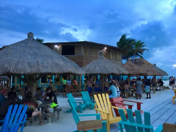Best Things to Do in Caye Caulker featured by top US travel blog, The Common Traveler: colored chairs in front with bar with palapas in background