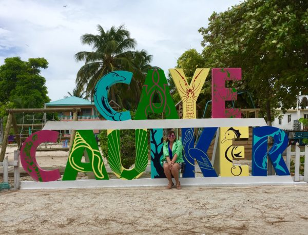One Week in Belize featured by top US travel blog, The Common Traveler: woman in front of Caye Caulker sign in Belize