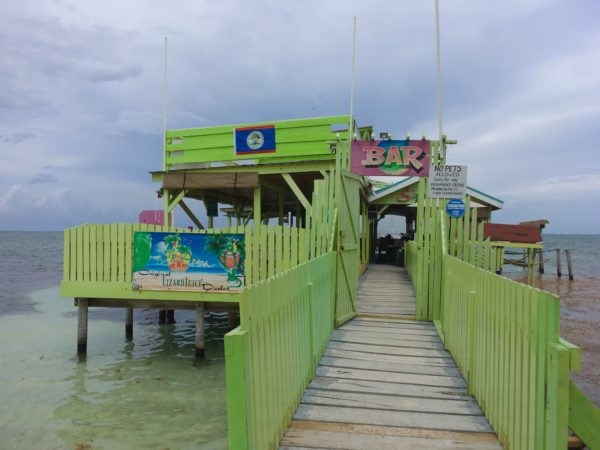 Best Things to Do in Caye Caulker featured by top US travel blog, The Common Traveler: dock with green bar on it