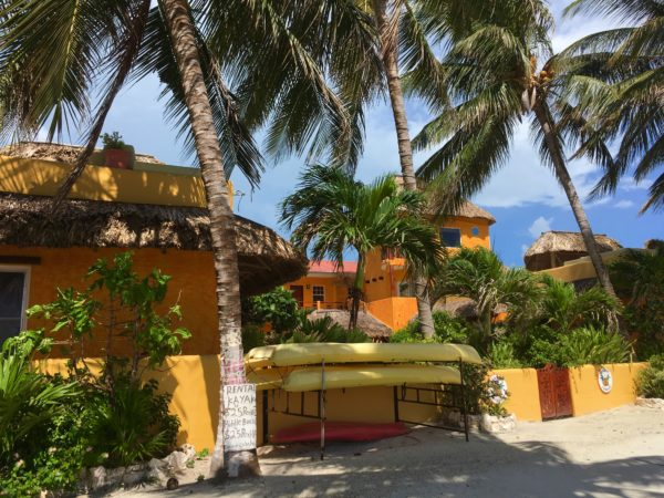Best Things to Do in Caye Caulker featured by top US travel blog, The Common Traveler: yellow and orange building with palm trees and kayaks in front