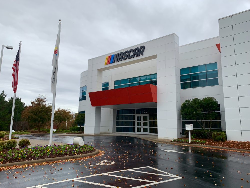 The best things to do in Concord NC in a weekend featured by top travel blog, The Common Traveler: white building with glass and red awning with NASCAR logo