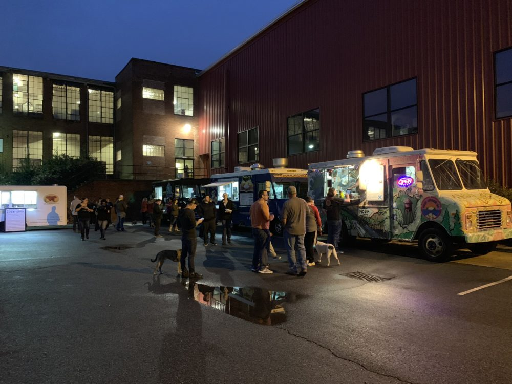 The best things to do in Concord NC in a weekend featured by top travel blog, The Common Traveler: food trucks with people waiting their turn outside old mill building