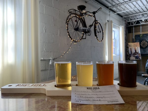 flight of beer on wooden paddle with old bicycle on wall in background - Red Hill Brewing, Concord, NC