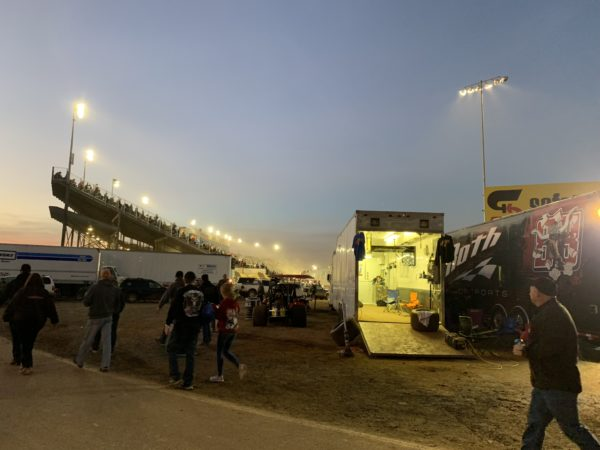 stand with lights and dirt with pit in foreground at World of Outlaws race