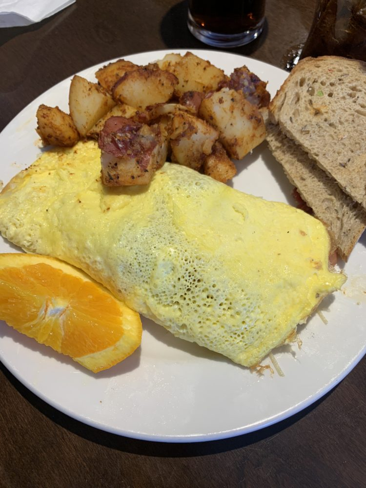 The best things to do in Concord NC in a weekend featured by top travel blog, The Common Traveler: plate with omelette, potatoes, toast and a piece of orange