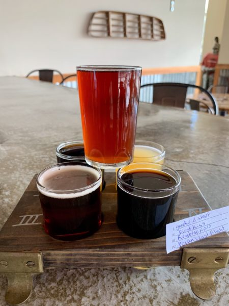 The best things to do in Concord NC in a weekend featured by top travel blog, The Common Traveler: flight of beer in front with old truck grill hanging on back wall