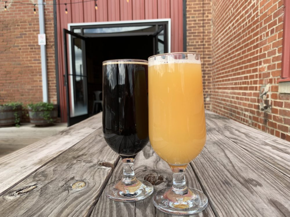 The best things to do in Concord NC in a weekend featured by top travel blog, The Common Traveler: two beers on wooden table in front of red door at Big Branch Brewing Company