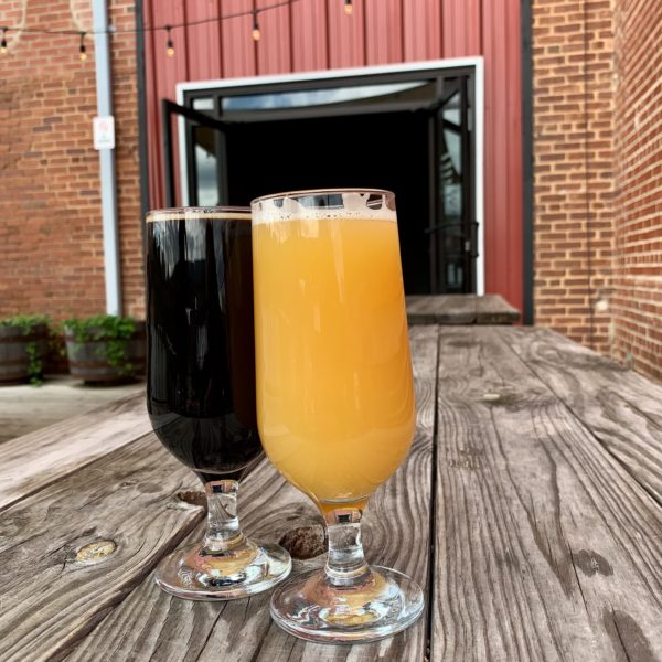 two glasses of beer in front of red building with open door - High Branch Brewing