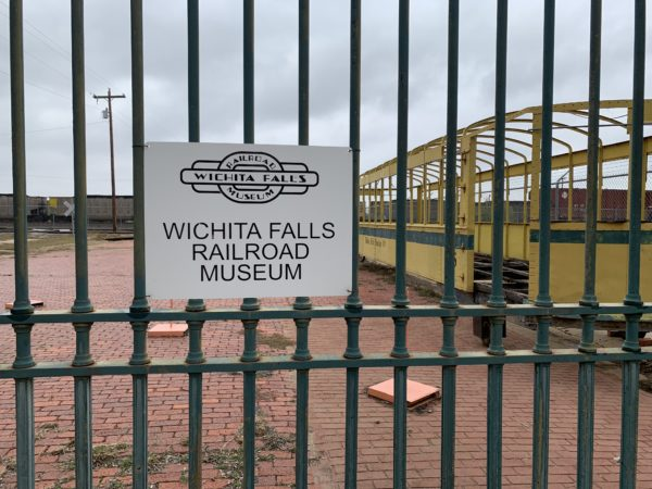 Wichita Falls Texas Itinerary featured by top travel blog, The Common Traveler: Wichita Falls Railroad Museum sign on metal bars