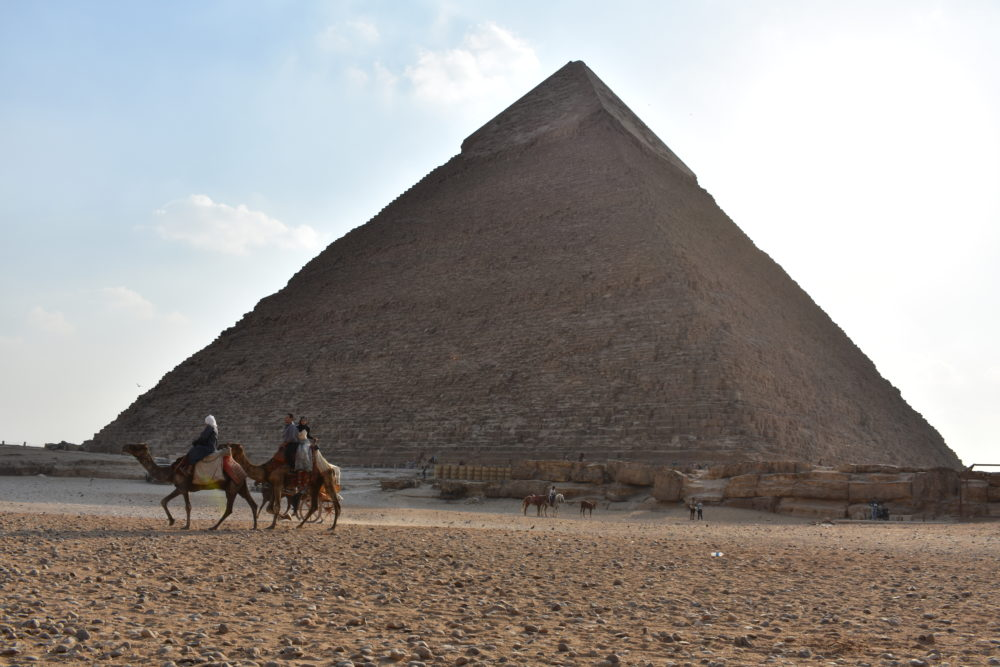 Travel bloggers' favorite places to visit in Asia and Oceania featured by top travel blog, The Common Traveler: pyramid with two camel riders in front