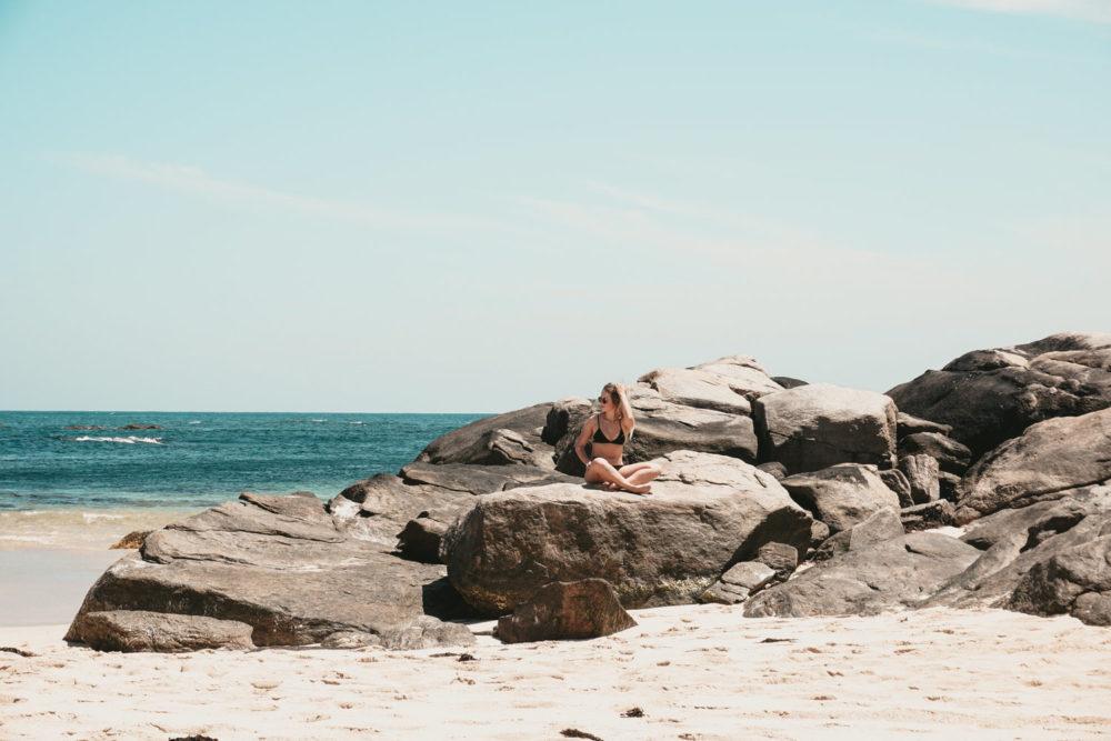 woman on rocks in Western Australia beach