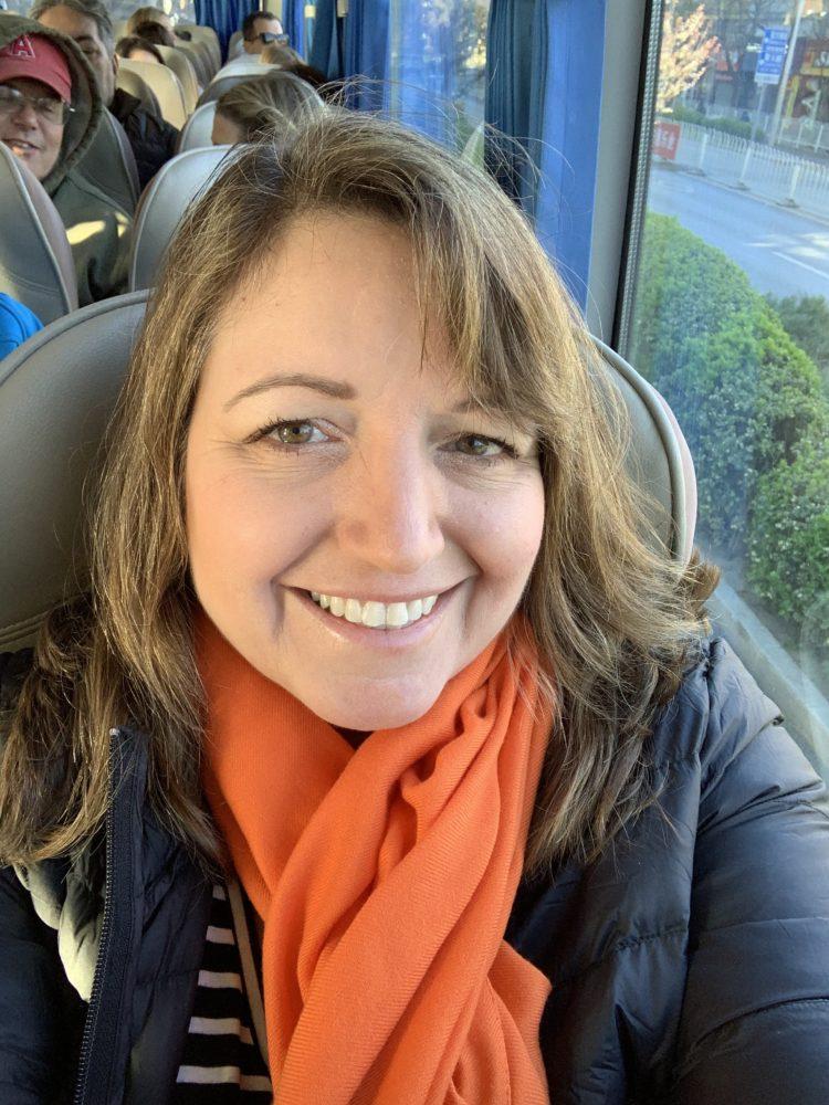 Woman smiling wearing black coat and orange scarf.