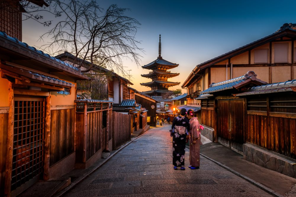 Japanese Geishas walking down street in Kyoto, Japan