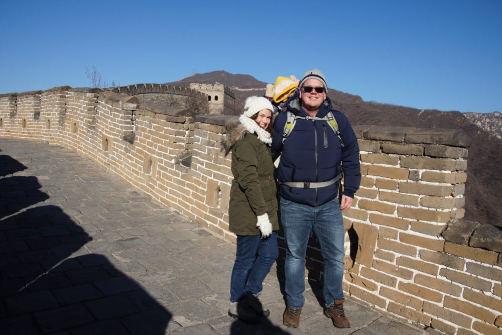 couple with baby standing on Great Wall of China