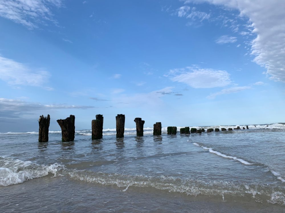 remaining stumps from old pier as waves hit beach