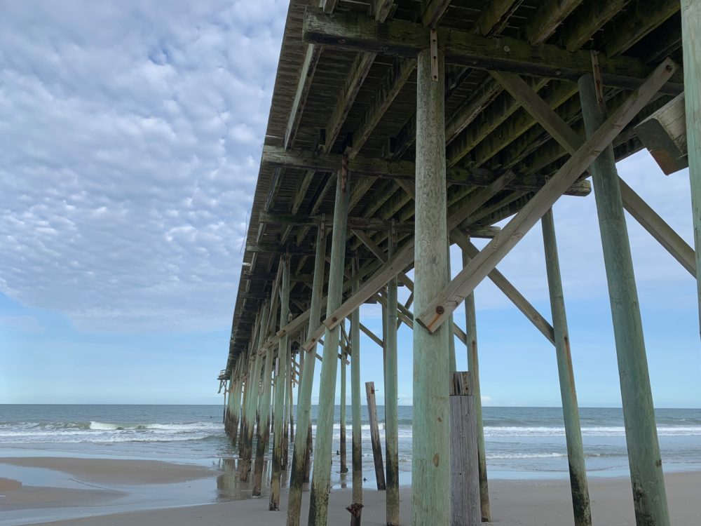 view of older fishing pier from underneath - with sand and ocean