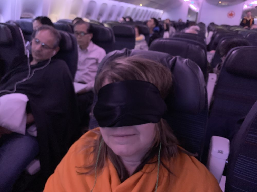 woman on plane with eye mask on