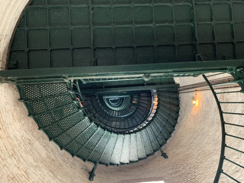 A Complete Tour of the Best North Carolina Lighthouses featured by top NC travel blog, The Common Traveler: green metal corkscrew staircase inside lighthouse