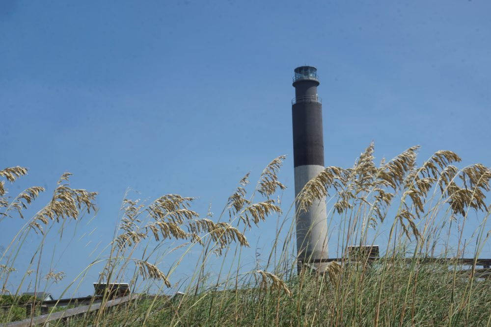 A Complete Tour of the Best North Carolina Lighthouses featured by top NC travel blog, The Common Traveler: Oak Island Lighthouse - light gray bottom half, black top half