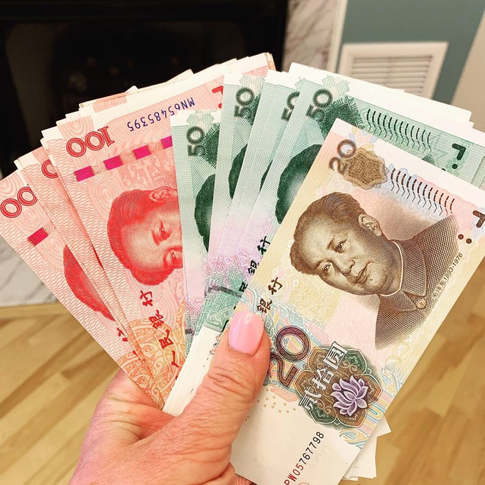 woman's hand holding Chinese Yuan