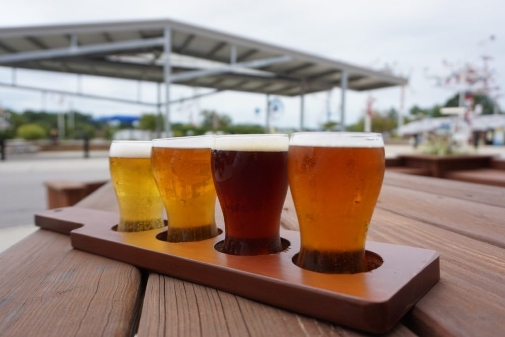 BEST VETERAN OWNED BREWERIES IN NC featured by top NC travel blog, The Common Traveler: flight of beers in front of whirlygigs at 217 Brew Works in Wilson, NC
