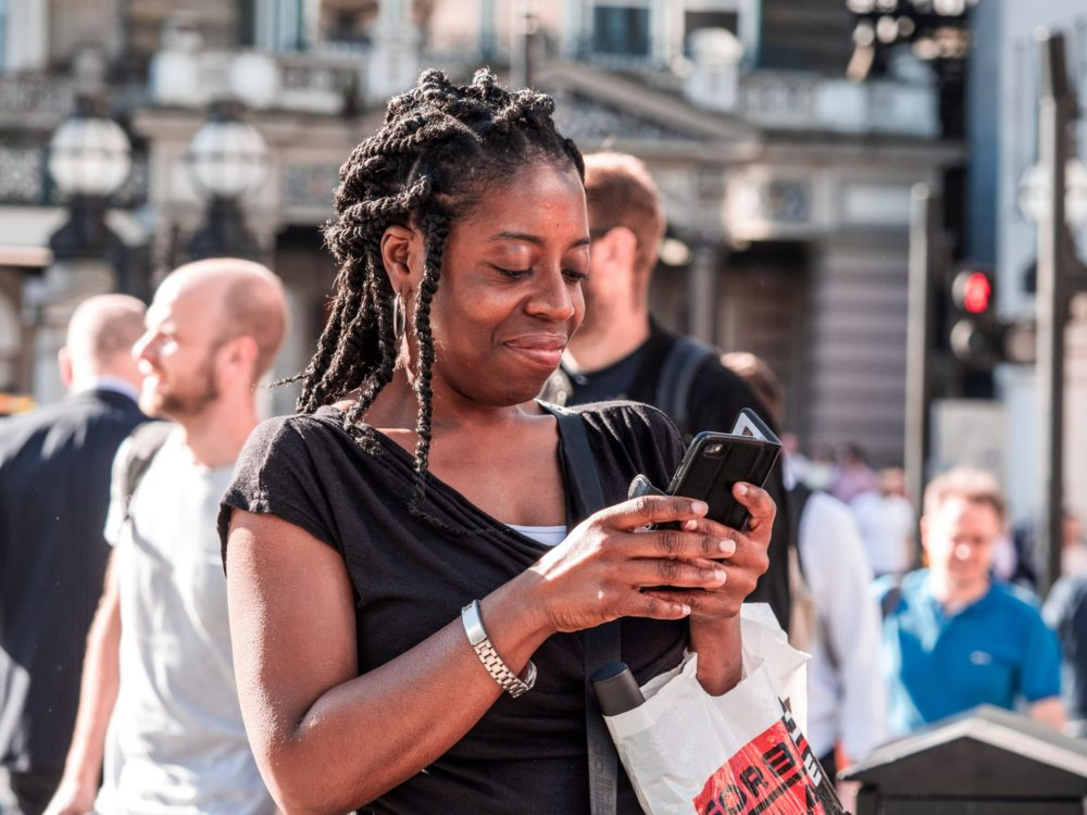 woman looking at phone screen in a crowd
